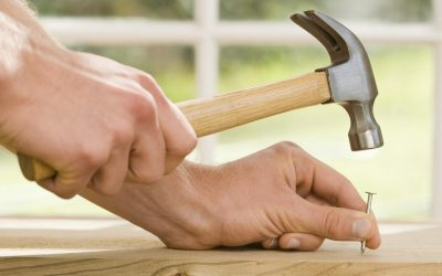 Hands hammering nail into wood